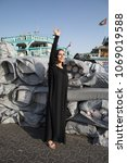 Small photo of A woman dressed in abaya goes by boats and sacks.