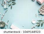 Beauty background with facial cosmetic products, leaves and cherry blossom on pastel blue desktop background. Modern spring skin care layout, top view, flat lay.