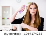 young woman spraying hair... | Shutterstock . vector #1069174286