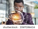 african male enterpreneur holds ...   Shutterstock . vector #1069186616