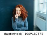 Small photo of Worried attractive young woman with long wavy red hair standing indoors biting her nail in trepidation looking to the side