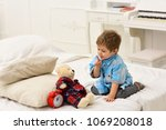 Small photo of Child in bedroom with silence gesture. Time to sleep concept. Boy with happy face puts favourite toy on bed, time to sleep. Kid put plush bear near pillows and alarm clock, luxury interior background.