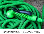 old green hose and water spray... | Shutterstock . vector #1069337489