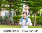 cute asian girl on neck dad big ... | Shutterstock . vector #1069354334
