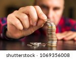 man counts his coins on a table.... | Shutterstock . vector #1069356008