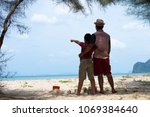 father and son with the beach... | Shutterstock . vector #1069384640