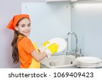 happy girl washes dishes at the ... | Shutterstock . vector #1069409423