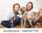 Stock photo attractive man and his young wife with pets two dogs and a cat a family portrait 1069447793