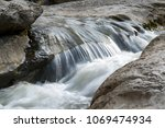 flow of the mountain river... | Shutterstock . vector #1069474934