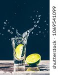 lime slice falls into a glass... | Shutterstock . vector #1069541099