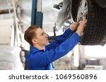 male mechanic changing car... | Shutterstock . vector #1069560896
