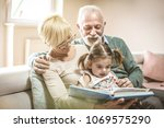 grandparents reading a book... | Shutterstock . vector #1069575290