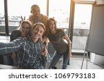 Small photo of Portrait of four happy people making snapshot of themselves at work. They are showing peace sign taking selfie in office