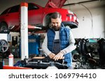 man mechanic repairing a car in ... | Shutterstock . vector #1069794410