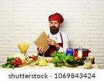 man with beard holds cook book...   Shutterstock . vector #1069843424