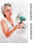 Small photo of A woman having a hot flash using a fan to cool off.