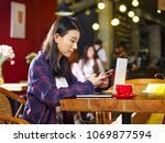 young asian woman sitting in... | Shutterstock . vector #1069877594