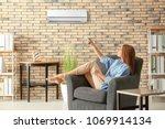 young woman switching on air... | Shutterstock . vector #1069914134