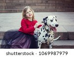 Stock photo young girl with her dalmatian dogs in a spring park sunset time red white and black 1069987979
