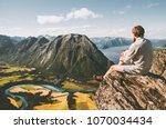 man sitting on cliff edge... | Shutterstock . vector #1070034434