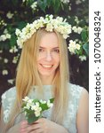 Small photo of Attractive modest young girl with blonde with jasmine flowers wreath on head long hair and natural make-up in white dress outdoors, tenderness and softness on nature background.