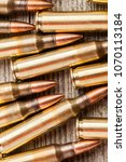 Small photo of Closeup top view of rifle full metal jacket bullets on wooden background
