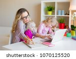 busy woman trying to work while ... | Shutterstock . vector #1070125520