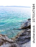 Small photo of The sea with crystal clear prosaic turquoise water beats against the rocks