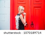 Young blond woman in black dress wear white angel wings behind her back in room against red doors .
