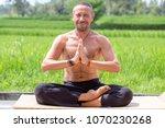 man doing yoga and meditating...   Shutterstock . vector #1070230268
