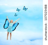 Happy Young Girl in Blue Dress with Arms in the Air Releasing Butterflies - stock photo