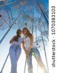two girls under an umbrella.... | Shutterstock . vector #1070383103