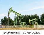 two active pumpjacks pumping... | Shutterstock . vector #1070400308