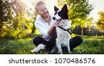 Stock photo man embracing his dog 1070486576