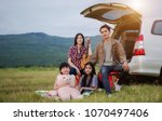 asian family sitting in the car ... | Shutterstock . vector #1070497406