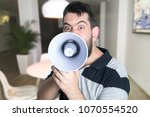 portrait of young man shouting... | Shutterstock . vector #1070554520