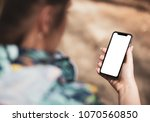 Small photo of Girl hand holding the black smartphone with big blank screen and modern frame less design in home interior, living room - isolated on white background angled position