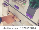 Small photo of Hand of woman recieve cash withdraw at ATM machine.