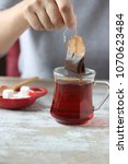 Small photo of hand holding tea bag, dipping a tea bag