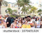 Small photo of LGBT crowd walks through the Miami Beach Gay Pride Parade 2018 after the parade finishes. The streets are crowded full of people wearing rainbow pride covered items.