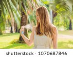 woman spraying insect repellent ... | Shutterstock . vector #1070687846