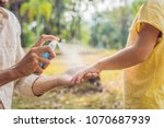 dad and son use mosquito spray... | Shutterstock . vector #1070687939