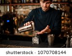 bartender pouring an alcoholic... | Shutterstock . vector #1070708144
