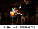 bartender pouring an alcoholic... | Shutterstock . vector #1070767286