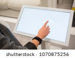 a woman touching the screen of... | Shutterstock . vector #1070875256
