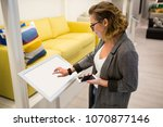 woman with phone configuring... | Shutterstock . vector #1070877146