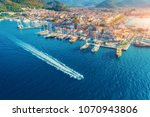 Aerial view of boats, yahts, floating ship and beautiful architecture at sunset in Marmaris, Turkey. Landscape with boats in marina bay, blue sea, city. Top view of harbor with yacht and sailboat.