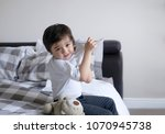 school boy sitting in bed and...   Shutterstock . vector #1070945738