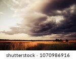 wheat field under dramatic sky... | Shutterstock . vector #1070986916