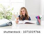child girl doing homework at... | Shutterstock . vector #1071019766